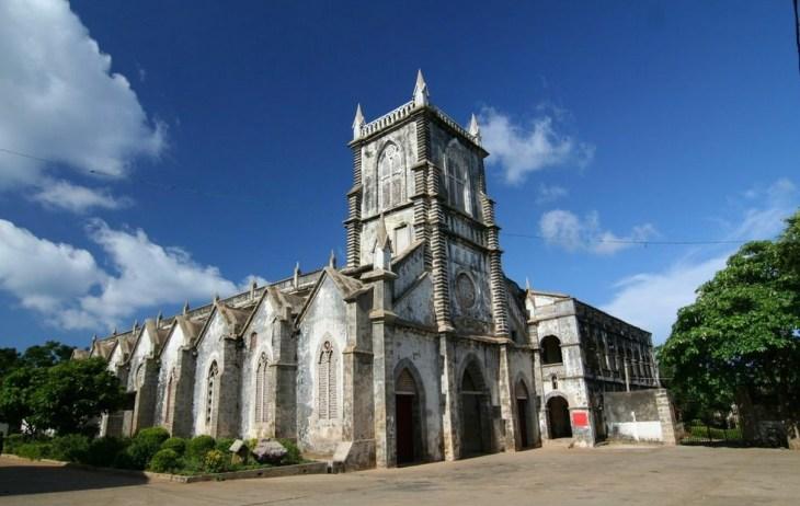 涠洲岛天主教堂位于涠洲岛盛塘村的天主教堂,掩映在一片绿影婆娑的芭蕉林和菠萝蜜树林中,是清末雷廉 地区一座最为宏伟的教堂。 高大雄伟的天主堂,在四周低矮民居的衬托下,显得规模庞大,颇有气势。正门顶端是钟楼,高耸着罗马式的尖塔,有着随时向天一击的动势,造成一种天国神秘的幻觉,堪称别具一格。 钟楼有一个10多级的石造螺旋梯,只容一人盘旋而上直达二楼。顶层挂有一口铸于1889年的白银合金大钟。据说是一法籍寡妇教徒所赠,当年的钟声能传遍整个涠洲岛。每个礼拜天的上午,司钟人上二楼拉响教堂的大钟,圣堂村及近邻